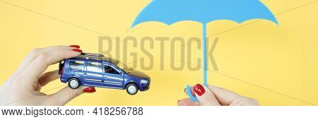 They Are Holding A Car And An Umbrella.