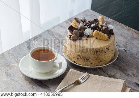 A Cup Of Tea On A Saucer And A Sponge Cake With Buttercream On The Marble Countertop. The Cake Is De