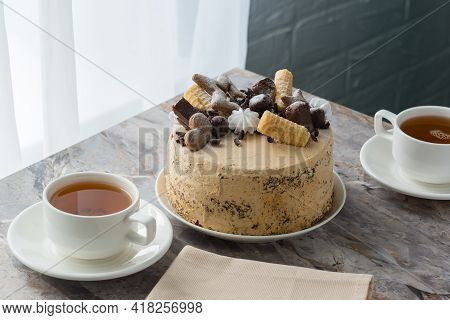 A Cup Of Tea On A Saucer And A Sponge Cake With Buttercream On The Marble Countertop In The Cafe Nea