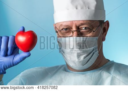 Portrait Of A Middle-aged Experienced Cardiologist Surgeon In Medical Clothing: Cap, Gloves, Robe An