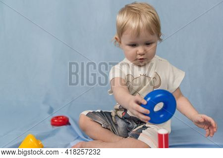 A Small Blonde Child Sits On A Blue Background And Plays With Toys
