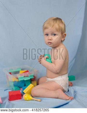A 1-year-old Girl In A White Diaper Sits On A Blue Background With A Multi-colored Constructor. The