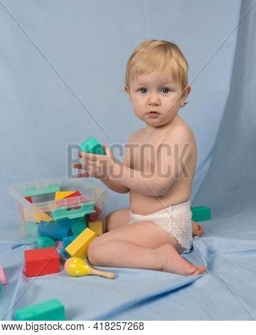 A Small Blonde Girl In A White Diaper Sits On A Blue Background With A Multi-colored Constructor. Th