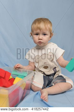 A Little Blonde Girl In A Short Jumpsuit With A Bear Pattern And Playing With Colorful Cubes Constru