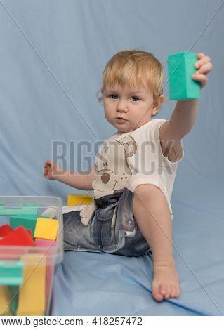 A Little Blonde Girl In A Short Jumpsuit With A Pattern And Playing With Colorful Cubes Constructor
