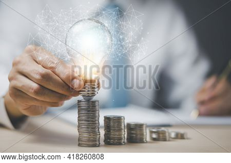 Businessman Hand Holding Light Bulb With Line Connect And Coins Stack On The Wooden Table, Saving Id