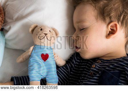 Authentic Portrait Sick Cute Caucasian Little Preschool Baby Boy In Blue Sleep With Teddy Bear On Wh
