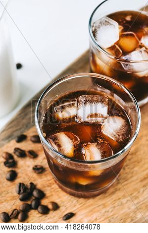 Ice Coffee Americano In Glass With Ice Cubes On Wooden Board, Close-up.