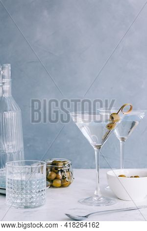 Martini Cocktail In A Glass On Blue Background With Olives.
