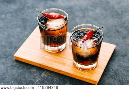 Whiskey And Cola In Glass Decorated Whit Dried Chili Peppers On Dark Background.
