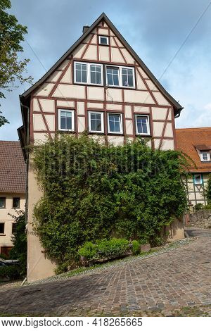 A Historic, Medieval Half-timbered House Overgrown With Ivy On A Descending Street. The Old German T