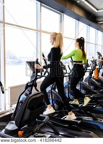 Beautiful Athletic Woman In The Sportswear Doing Fitness Cardio Exercises In The Gym On Stepper Mach