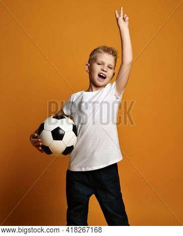 Screaming Loudly Blonde Kid Boy In White Blank T-shirt Stands Holding Soccer Ball In Hand And Gestur