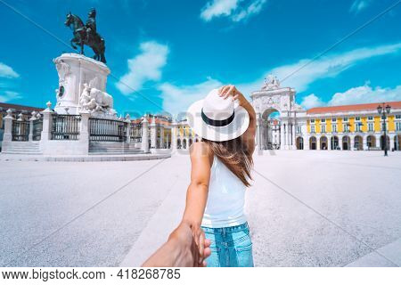 Tourist Woman In White Hat Holding Hand Of Her Boyfriend And Exploring Lisbon City Together. Couple