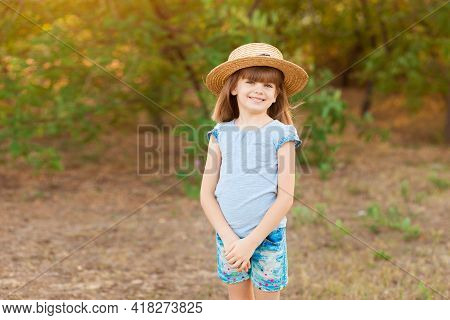 Adorable Child Girl In Straw Hat Spending Time Outdoor On A Summer Day. Happy Portrait Of Shy Smilin