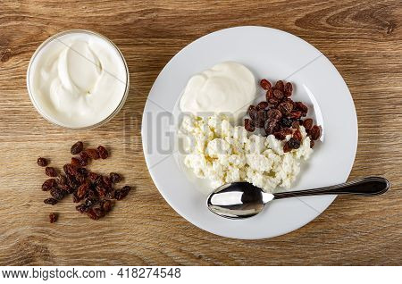 Transparent Glass Bowl With Sour Cream, Scattered Raisin, Spoon In White Plate With Cottage Cheese,
