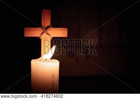 Wood Cross By Candlelight. Light Of Faith Is Shining In Darkness Of Unbelief. Concept Of Christianit