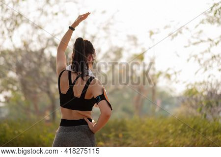 Athletic Woman Warming Up Before A Workout Standing Facing The Early Morning Rising Sun At Park