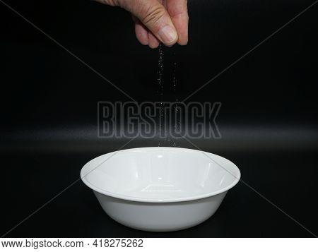 Hand Sprinkling Salt Into Bowl Against Black Background