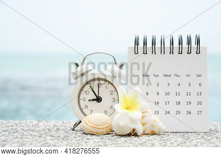 White Analog Clock And Opened Calendar With Blurred Shell And Plumeria Flower On Blurred Sea Backgro