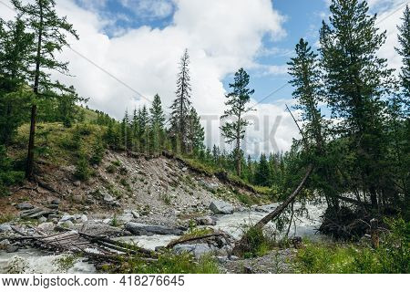 Powerful Rapids In Fast Turbulent River With Broken Bridge In Water. Scenic Green Forest Landscape W