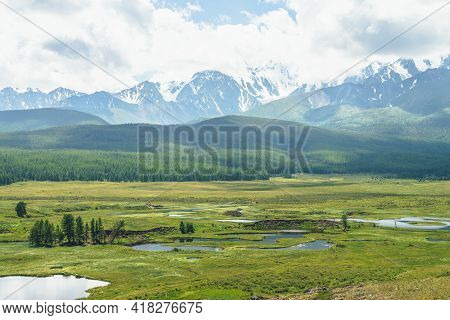 Beautiful Green Scenery With Lake System On Tableland Among Forest Hills And Snowy Mountains. Scenic