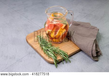 Summer Homemade Drink With Grapefruit And Rosemary. A Transparent Glass Jug With Grapefruit Wedges A