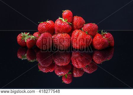 A Horizontal Shot Of A Pile Of Red Croatian Strawberries On A Black Reflecting Surface
