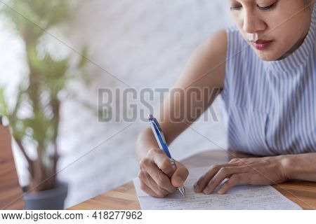 Business Women Use Pen Writing Document Paper. Female Hand Close Up Writing With A Blue Pen On A Whi
