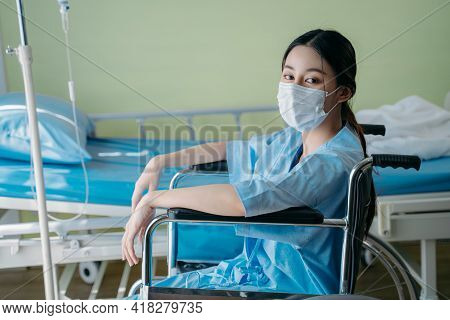 Portrait Of Asian Young Handicapped Woman With Sad And Hopeless Feeling Sitting On Wheelchair Alone