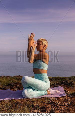 Sunrise Outdoor Yoga. Young Woman Practicing Gomukhasana, Cow Face Pose. Seated Asana In Hatha Yoga.