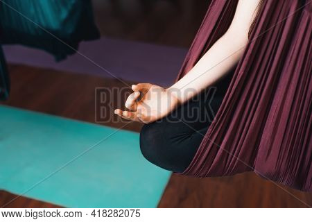 Woman Practicing Meditation In A Hammock Indoors. Close-up Of A Female Hand, Selective Focus. Anti-g