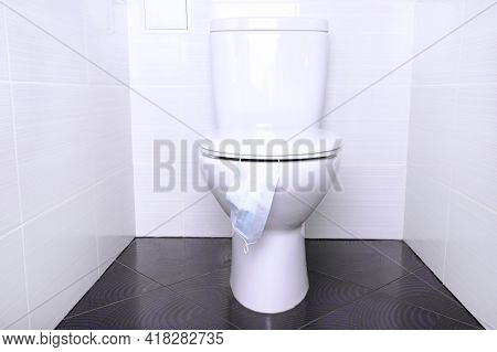 White Home Toilet With Flush And Disposable Medical Mask In The Bathroom. Quarantine Concept.