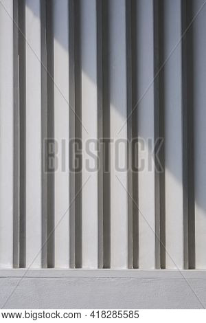 Sunlight And Shadow On Surface Of White Wooden Sunshade Battens On Cement Wall In Vertical Frame