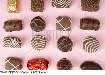 Top View Of Various Chocolate Pralines On Pink Background. Collection Chocolates Candy. Assorted Cho