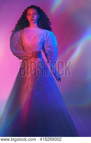 Art portrait of a refined female model with lush red curly hair posing in a long white futuristic dress in neon mixed red color lighting.