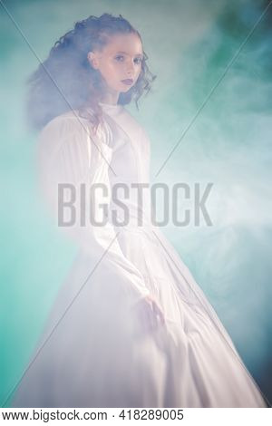 Art portrait of a refined female model with lush red curly hair posing in a long white futuristic dress among haze on green backgrount.