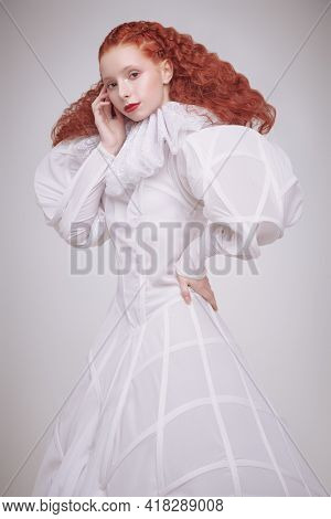Art portrait of a refined female model with lush red curly hair posing in a long white futuristic dress on light grey background.