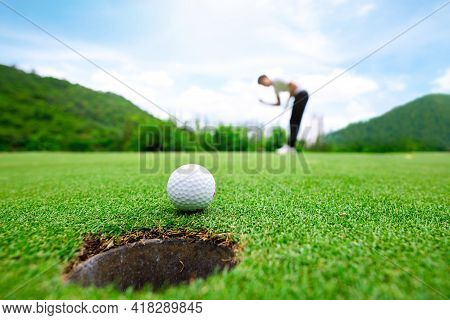 Man Putting Golf Ball On The Green Golf.,close Up In Golf Coures