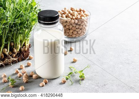 Vegetable Pea Milk In A Bottle And Chickpeas On A Light Gray Concrete Background. Gluten-free, Lacto