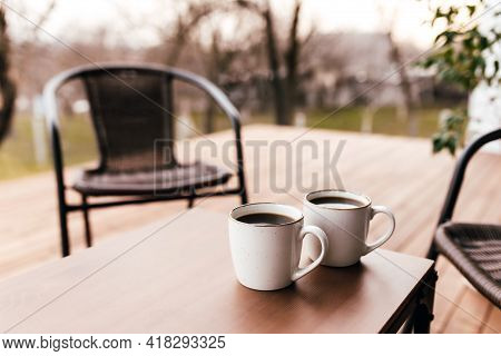 Two Cups Of Coffee On The Table On The Wooden Brown Terrace During Evening Sunset. Relaxation, Lover