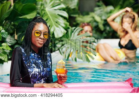 Portrait Of Smiling Young Black Woman In Full Body Coverage Swimsuit And Yellow Sunglasses Standing