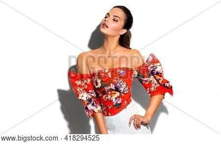 Beauty fashion model girl in trendy wear, with bright make-up, brunette woman isolated on white background, posing. Street Fashion outfit look. Beautiful young brunette woman with trendy accessories.