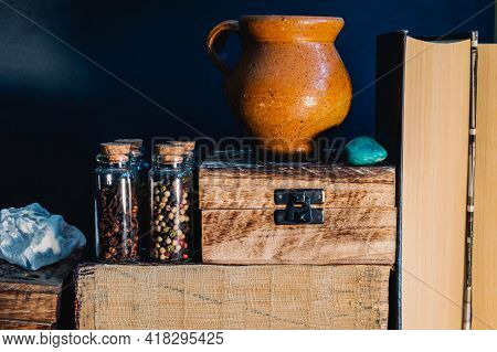 Still Life Image Of Books, Wooden Boxes, Glass Stopper Bottles With Spices An Earthenware Jug And Se