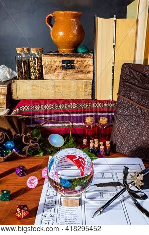 Rpg Witchcraft Scene Of A Desktop With Polyhedral Dice, A Crystal Ball, Game Sheet, Potions, Feather