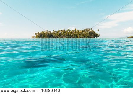 Deserted Island paradise. Travel vacation icon of tropical beach private island motu with palm trees. French Polynesia Boat excursion in turquoise lagoon ocean going to private island in Bora Bora.