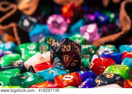 Close-up Image Of A Black And Red Marbled 20-sided Die On A Pile Of Various Colored And Shaped Dice