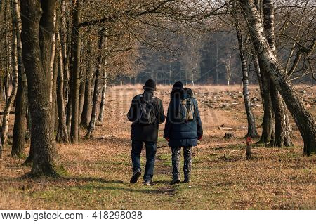 Two People With Small Backpacks, Wearing Thick Winter Coats And Warm Woolen Hats Walking To The Fore