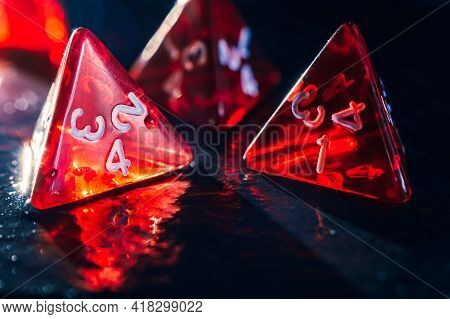 Close-up Of Four Red Transparent 4 Sided Dice On A Wet Slate Surface. Focused On The Foreground. Len