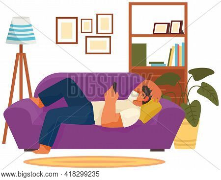 Guy Playing On Smartphone Is Lying On Couch Indoors. Man Relaxing At Home Alone. Living Room Interio